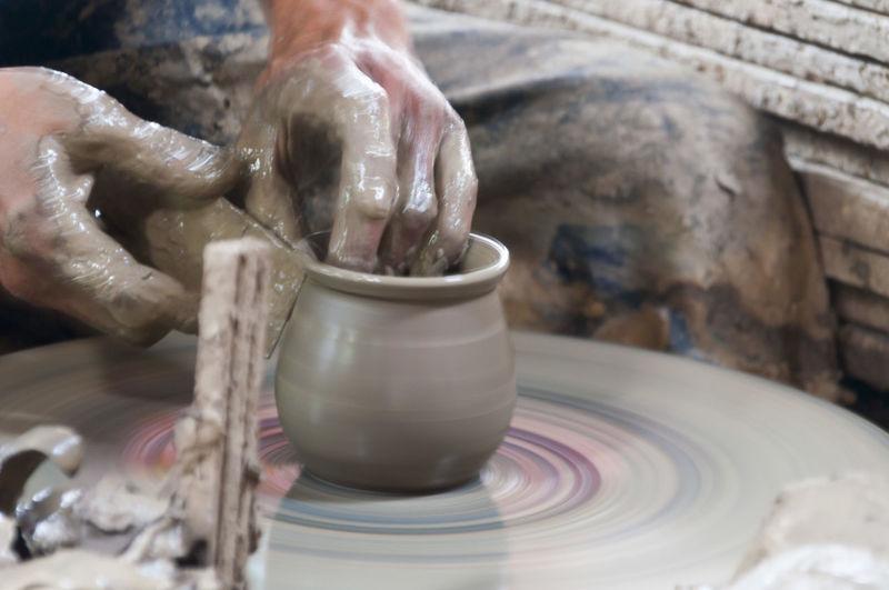 Midsection Of Potter Making Pot At Workshop