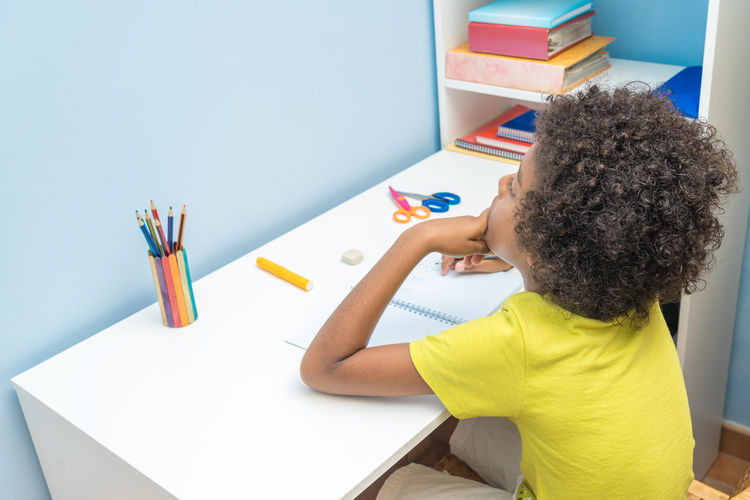 High angle view of boy holding multi colored pencils on table