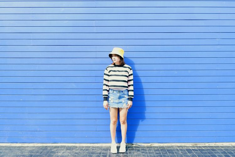 Portrait of girl standing against blue wall