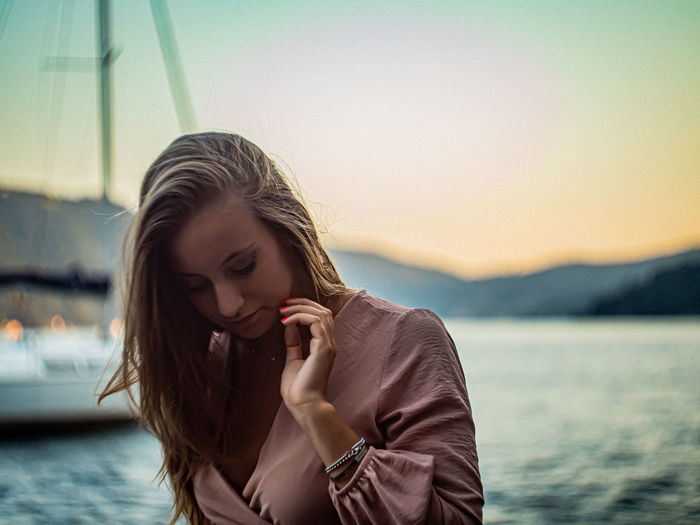 Portrait of young woman looking at lake against sky