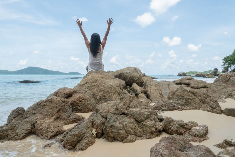 Rear view of person on rock at beach against sky