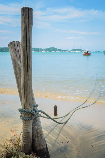 A rope of a boat is tie up with wooden stake on the beach