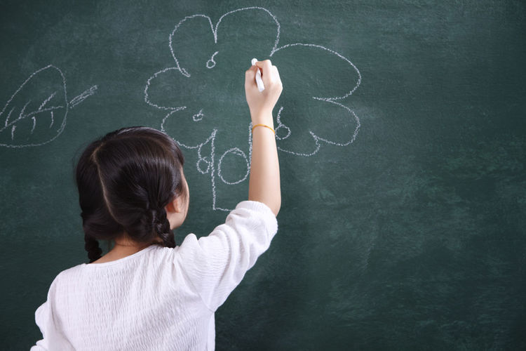 Rear View Of Girl Drawing On Blackboard
