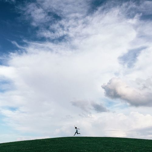 Low angle view of person jumping on grassy hill against cloudy sky