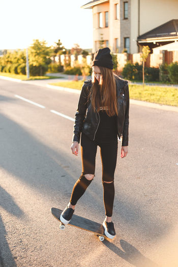 Young woman with skateboard standing on road during sunny day
