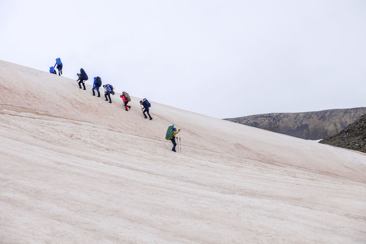 People walking on snowy mountain against clear sky