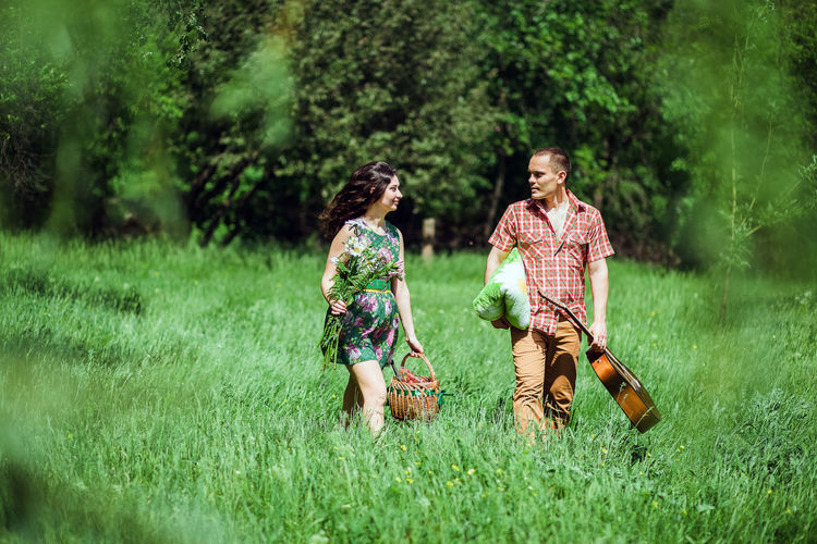 Couple with guitar and basket walking on grassy land