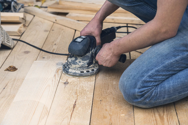 Low section of man working on wooden floor