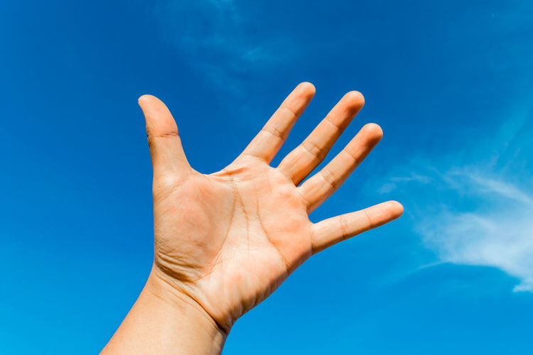 Cropped Hand Gesturing Against Blue Sky