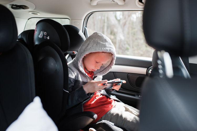 Rear view of boy sitting in car