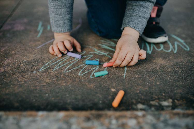 Child drawing with colored chalk on the floor