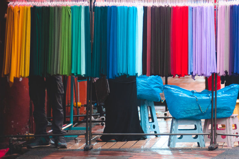 Low Section Of People Standing Behind Multi Colored Fabrics Hanging On Rack