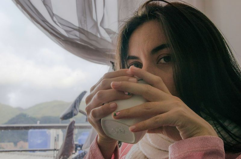 Close-up portrait of young woman drinking coffee at home