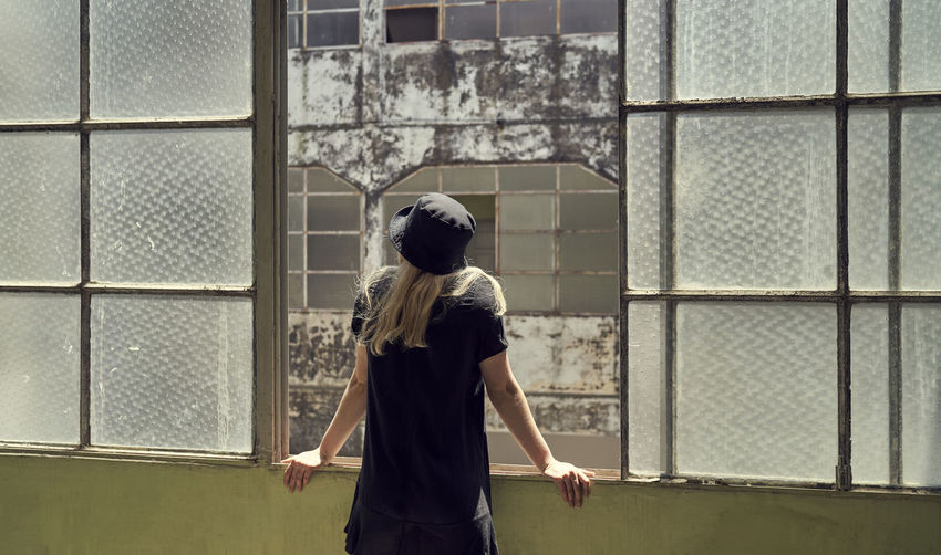 Rear view of woman in black dress standing with blonde hair against old window