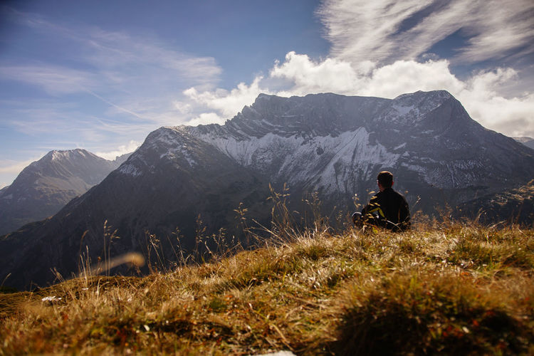 Man sitting on grassy field against mountains during sunny day
