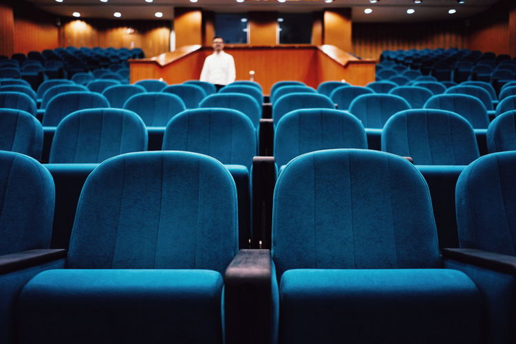Defocused mid adult man standing amidst blue empty chairs in auditorium