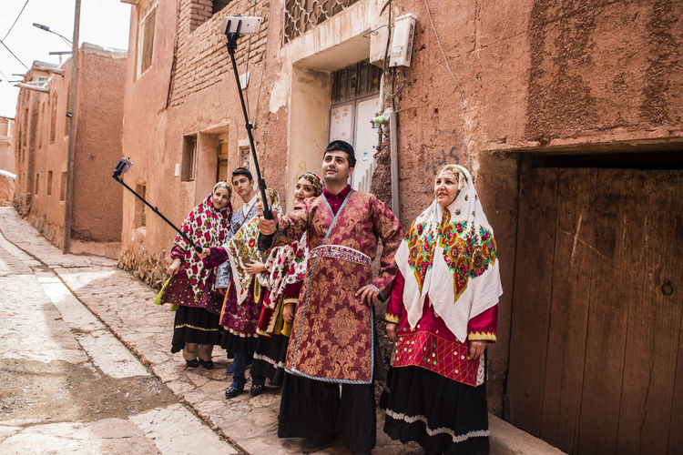 Men with women in traditional clothing taking selfie at alley