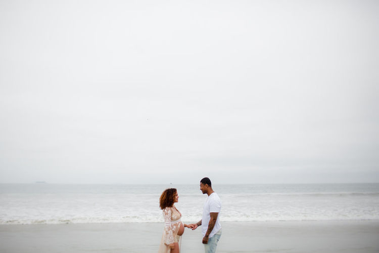Rear view of couple on beach against sky