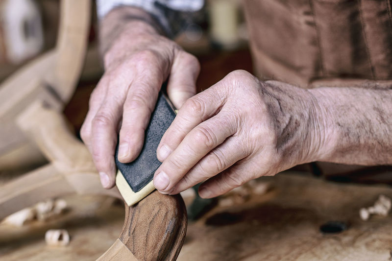 Close-Up Of Carpenter Polishing Wood In Workshop