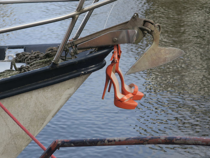 Close-up of rope hanging on railing by river