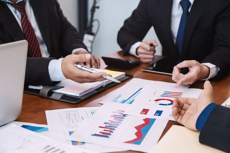 Midsection of businessman and colleague working over graphs on table