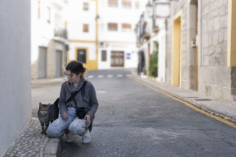 Teenage girl with her photo camera greeting a street cat in the town of Altea, in the province of Alicante, Spain. Alicante Altea Animal Domestique SPAIN Spanish Travel Animal Cat Caucasian Lifestyles Love For The Animals One Animal One Person People People Photography Peoplephotography Pets Street Street Cat Stretphotography Teen Teenager Travel Destinations Women Young Women