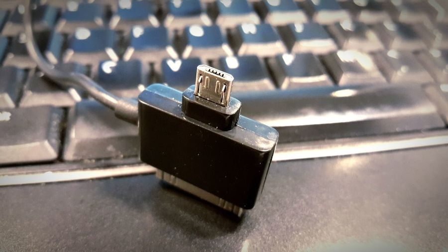 Close-Up Of Network Connection Plug By Keyboard On Table
