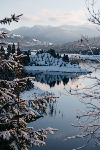 Picture taken at Colibita, Romania. Winter of 2019. Beautiful sunrise, beautiful weather, clear sky, blue water. www.instagram.com/pontosanpele Water Nature Mountain Reflection Winter Snow Cold Temperature No People Scenics - Nature Sky Cloud - Sky Lake Outdoors Pine Tree Tree Mirror Lake Blue Water Clouds Transylvania Romania Balkan Travel Destinations Backpack Sunrise Sunrise_sunsets_aroundworld