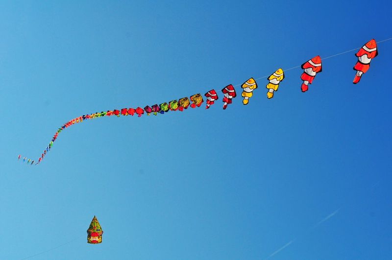 Low angle view of kites flying against clear blue sky