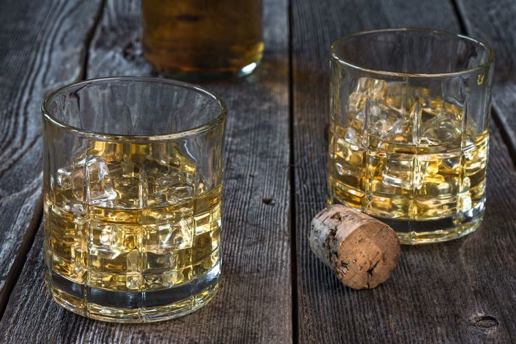 Two glasses of bourbon on a rustic table Bourbon Whiskey Gold Lowball Glasses Alcohol Libation Whiskey Whisky Beverage Drink Adult Masculine Rustic Rum Close-up