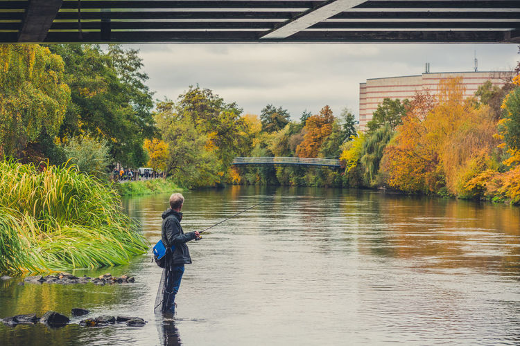 Fisherman in Bamberg Architecture Autumn Autumn Colors Bamberg  Beauty In Nature Built Structure Childhood Day Deutschland Fall Fisherman Fishing Fishing Net Germany Nature One Person Outdoors People Real People Rear View Regnitz River Tree Water Water Reflections