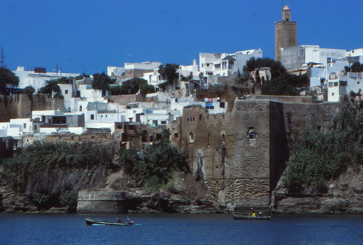 Low Angle View Of Buildings By Sea Against Clear Sky