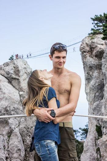 Portrait of shirtless boyfriend embracing girlfriend against rock formation