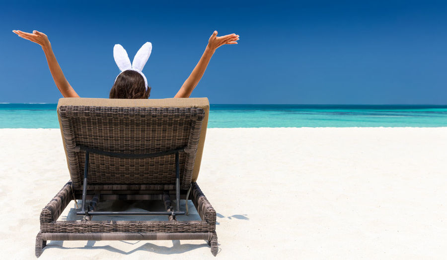 Woman with arms raised relaxing on lounge chair at beach against blue sky