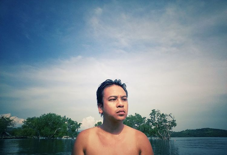 Portrait of shirtless young man standing against lake