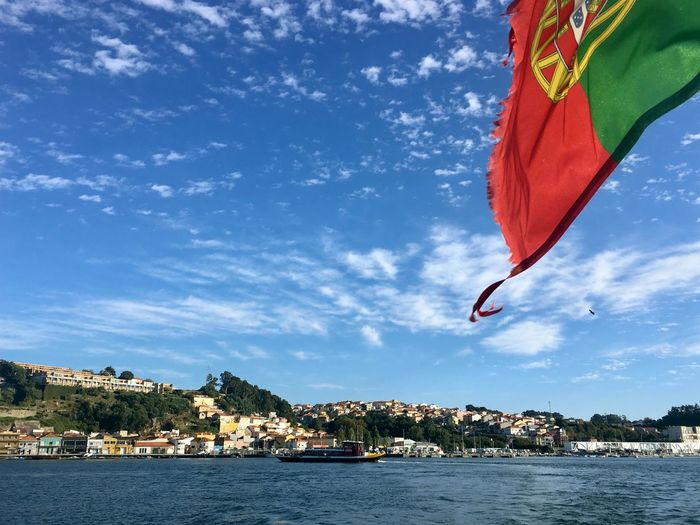 Scenic view of a portuguese flag at the back of a boat with blue sky and a small village in the back