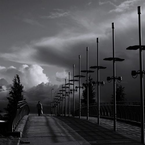 The road ahead Streetlights Dark Sky Storm Brewing Storm Cloud Uncertainty  Alone Street Photography Streetphoto_bw Street Streetphotography Black And White Sky Cloud - Sky Real People Street Street Light City One Person Direction Footpath The Way Forward Walking Rear View My Best Photo