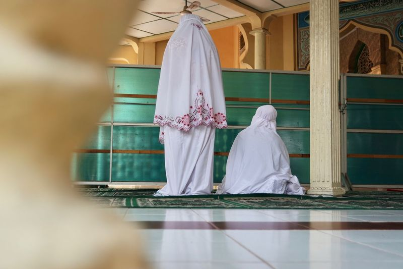 Rear view of women wearing traditional dress praying in mosque
