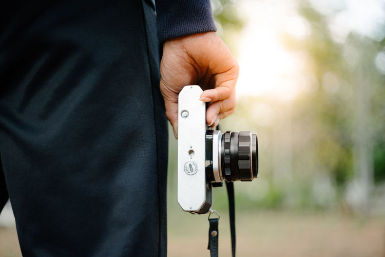 Midsection of man holding camera while standing outdoors