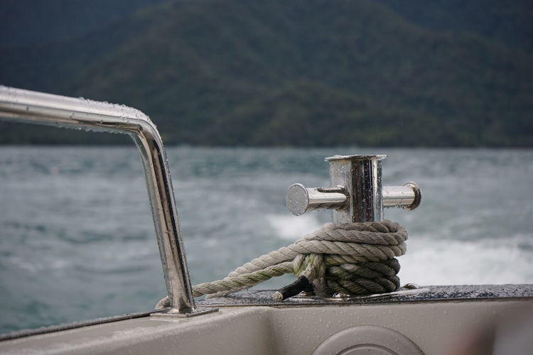 Close-up of rope tied on railing against sea