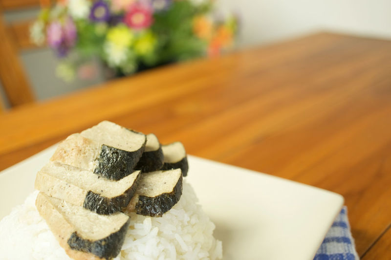 Vegetarian fried salted fish slice and white rice with blue fabric on wood table and blur flower as background. Cuisine Green Rice Seaweed Vegetarian Wood Alga Bean Black Blue Brown Chinese Fabric Flower Food Fried Ingredient Plate Restaurant Salted Fish Slices Table Tofu Vegetable White