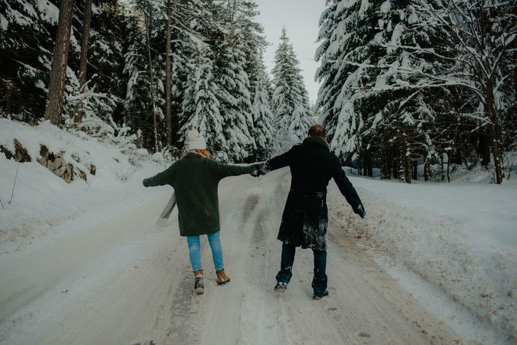 Rear view of friends walking on snow covered trees