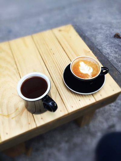 Close-up of cappuccino and black tea on wooden table