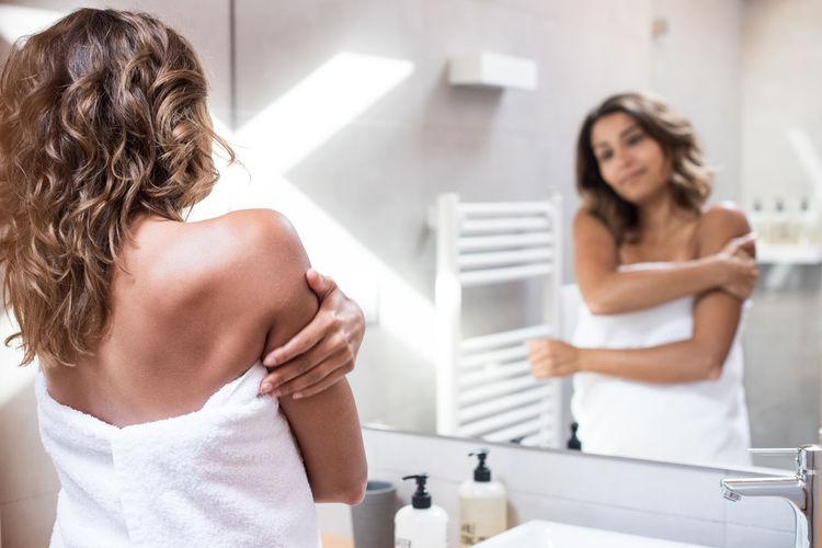 Rear view of women standing in bathroom
