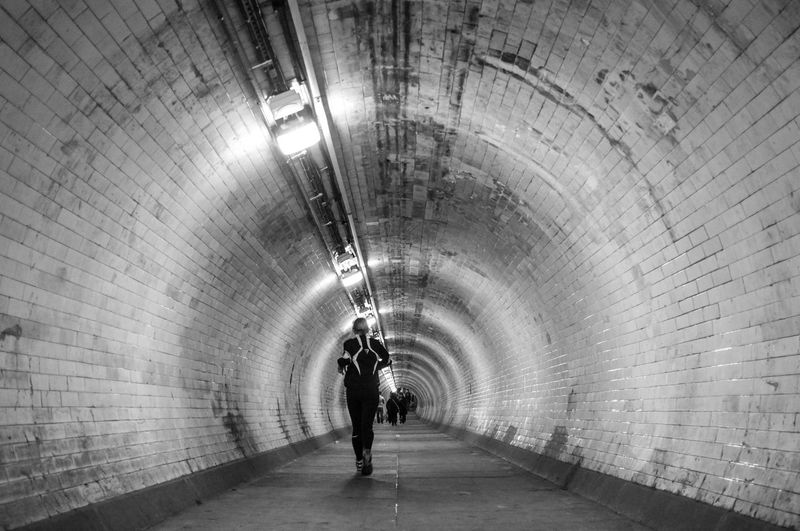 Rear view of woman running in tunnel