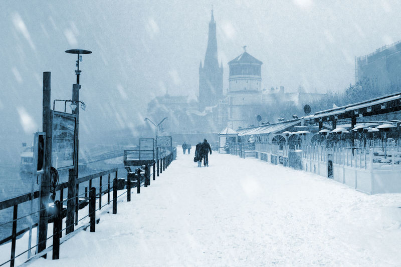 Rear view of people walking on snow covered street in city during winter