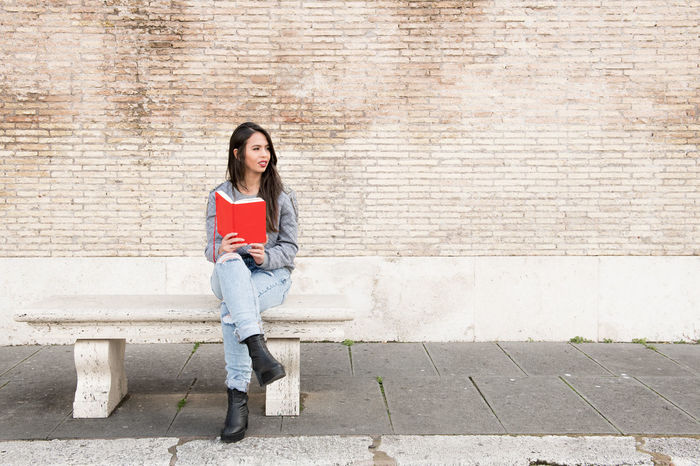 Young pretty woman sitting outdoor with red book Bench Red Book Sitting Wall Book Brazilian Brunette Casual Clothing Cheerful Latina Woman Long Hair Portrait Reading A Book Urban Young Adult Young Woman