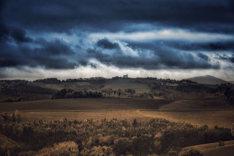Scenic View Of Landscape Against Storm Clouds
