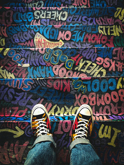 Low section of person standing on multi colored text on staircases