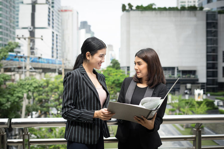 Smiling businesswomen looking at folder while standing against buildings in city